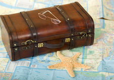Old Retro Suitcase, Map, Starfish. An old retro-styled suitcase made of brown wood and leather, eye glasses, starfish, on top of a map of Florida royalty free stock image