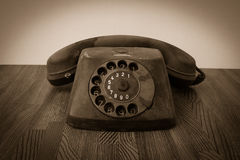 Old retro telephone on table. Vintage style sepia Stock Photos