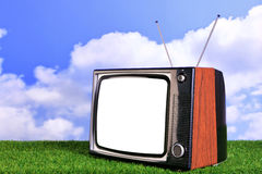 Old retro TV outdoors. Photo of an old retro TV outdoors on grass with blue sky and white clouds in the background, blank screen with clipping path to add your Stock Images