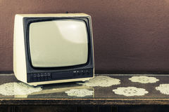 Old retro TV on vintage table, brown background Stock Photo