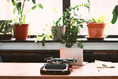 Old retro typewriter on wooden desk. Laptop on table royalty free stock photography