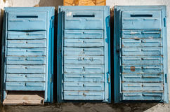 Old retro vintage blue metal mailboxes for letters and newspapers hanging on the wall of an apartment house Stock Images