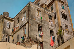 Old ,retro vintage building with various clothing in open windows on Cuban Havana street against blue sky Royalty Free Stock Photo