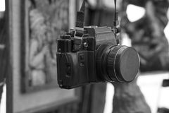 Old retro vintage film camera on a neck strap. Old retro vintage black film camera with lens attached hanging on a neck strap. black and white image with blurred stock photo