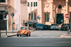 Old Retro Vintage Orange Color Volkswagen Beetle Car Moving At Street. Rome, Italy - October 21, 2018: Old Retro Vintage Orange Color Volkswagen Beetle Car royalty free stock photo