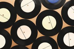 Old retro vinyl records on beige background, top view. Old black vintage vinyl records with white label on beige background. Top view on retro media plates, copy Royalty Free Stock Photo