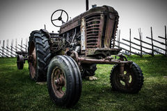 Old retro wheeled tractor. Eaten away with rust, standing in a field, fenced in. Outdoor royalty free stock images