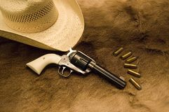 Old Revolver. An old western revolver with ammo and a hat on top of an old deer skin Stock Photography