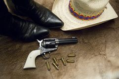 Old Revolver and Boots. An old revolver with black boots and a hat on top of an old deer skin Stock Photo