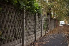 The old pattern of the fence in autumn. The old rickety fence of the Park among autumn leaves Stock Photography