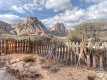 Old rickety wood picket fence in an arid landscape. Old rickety wooden picket fence in an arid semi-desert landscape with broken wagon wheel and rocky mountain Royalty Free Stock Photo