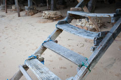 Old rickety wooden stairs leading to the sandy beach. The old rickety wooden stairs leading to the sandy beach on the background of the dog prints Royalty Free Stock Images