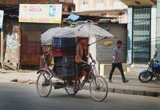 Old Rickshaw Driver Brings Many Baskets in Kathmandu Royalty Free Stock Photos