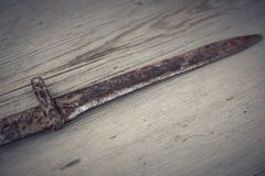 Old rifle`s bayonet. On a wooden background royalty free stock image