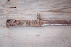 Old rifle`s bayonet. On a wooden background stock images