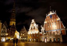 Old Riga at night. Beautiful old architecture of the central square of Riga. Night view with illuminated buildings and people silhouettes Royalty Free Stock Photo