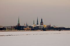 Old Riga panorama over frozen. Riga Old Town panorama at dusk viewed over frozen Daugava river covered by deep snow Stock Images