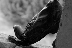 Old ripped boot on window black. Ripped military boot on window Stock Photos