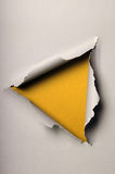 Old Ripped Paper Forming Triangle. Over yellow background royalty free stock image