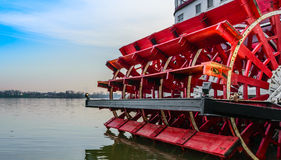 Old Riverboat Paddle Wheel. Red paddle wheel on a smooth wide river stock image