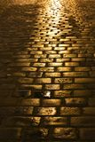 Old road. Old brick road in the night after rain, reflecting light Royalty Free Stock Images