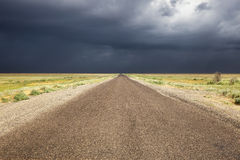Old road in desert and storm sky Royalty Free Stock Photo