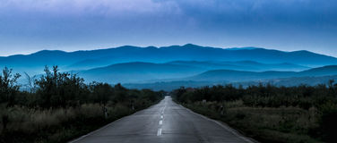 Old road leading to the blue hills Royalty Free Stock Photos
