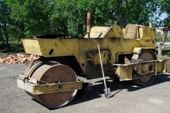 An old road roller stands next to the green trees. royalty free stock images