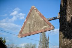 Old road sign. Old dirty post apocalyptic triangular road sign Royalty Free Stock Photography