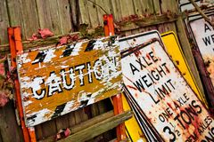 Old Signs. Old road signs and caution signs laying against a wooden fence. Axle Weight Limit one axle 3 1/2 tons royalty free stock photos