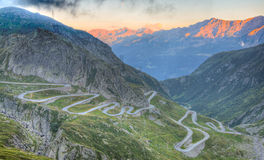 Old road with tight serpentines. On the southern side of the St. Gotthard pass bridging swiss alps at sunset Royalty Free Stock Photos