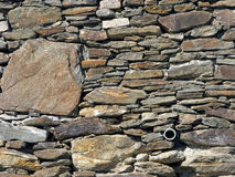 Old Rock Wall with Drainage Pipe. Royalty Free Stock Photo