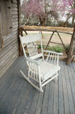 Old Rocking Chair. Old replica rocking chair or is the real thing, sitting on the front porch of old historic western house Stock Photos