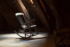 Old Rocking Chair. On a dim attic stock images
