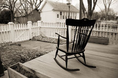 Old Rocking Chair on wooden porch with white picket fence. This black and white photo of an old rocking chair sitting on a wooden porch, surrounded by a white Stock Photo