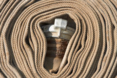 Old rolled fire hose with nozzle Stock Image
