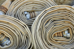 Old rolled fire hoses with nozzles Royalty Free Stock Image
