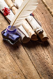 Old rolls of paper and blue ink in the inkwell. On old wooden table royalty free stock photo