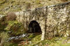 Old Roman bridge over river. Scenic view of old arched Roman bridge over river in countryside Stock Photography