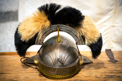 Old Roman helmet. Black and white, on wooden desk Stock Photography