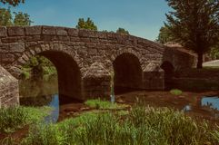 Old Roman stone bridge over the Sever River in Portagem. Old Roman stone bridge over the Sever River with green plants on the bank, in a sunny day at Portagem. A stock photo