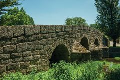 Old Roman stone bridge over the Sever River in Portagem. Old Roman stone bridge still in use over the Sever River with green plants on the bank, in a sunny day royalty free stock photography