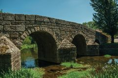 Old Roman stone bridge over the Sever River in Portagem. Old Roman stone bridge still in use over the Sever River with green plants on the bank, in a sunny day royalty free stock image