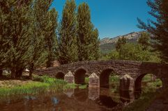 Old Roman stone bridge over the Sever River in Portagem. Old Roman stone bridge still in use over the Sever River, among leafy trees on sunny day at Portagem. A stock photos