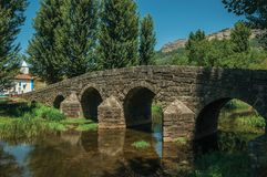 Old Roman stone bridge over the Sever River in Portagem. Old Roman stone bridge still in use over the Sever River, among leafy trees and undergrowth in a sunny royalty free stock image
