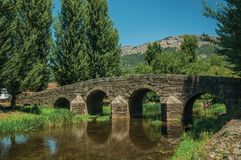 Old Roman stone bridge over the Sever River in Portagem. Old Roman stone bridge still in use over the Sever River, among leafy trees and undergrowth in a sunny stock photos