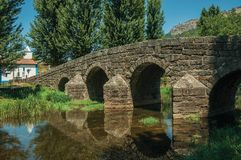 Old Roman stone bridge over the Sever River in Portagem. Old Roman stone bridge still in use over the Sever River, among leafy trees and undergrowth in a sunny stock photo