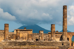 Old Roman temple. The columns of Jupiter temple in the forum of Pompeii, an old Roman city. Volcano Vesuvius in the background Stock Images