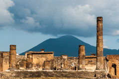 Old Roman temple. The columns of Jupiter temple in the forum of Pompeii, an old Roman city. Volcano Vesuvius in the background Stock Photos