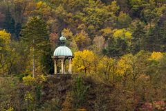 Romantic altar in autumn country. Old romantic altar on a hill in autumn landscape of yellow-green leaves Stock Photos
